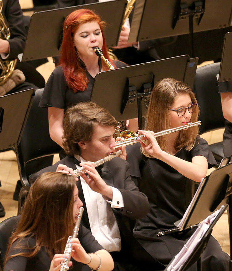 Male and female students playing their assortment of woodwind instruments onstage at Carnegie